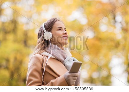 season, technology and people concept - beautiful happy young woman with headphones listening to music on smartphone walking in autumn park
