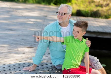 family, generation, communication and people concept - happy grandfather and grandson sitting on river berth