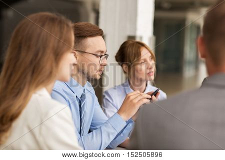 business, technology, communication and people concept - businessman texting on smartphone at office