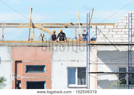 LYAKHOVICHI, BELARUS - AUGUST 28, 2016: Workers builders make installation of scaffolding