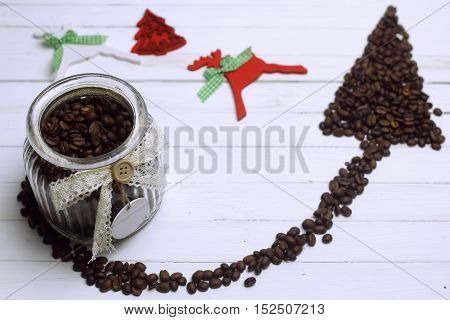 coffee beans in a glass jar on a wooden white background