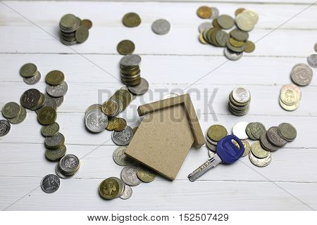 scattering of coins on a white wooden table and key as symbol of safety