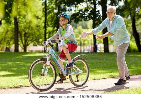 family, generation, safety and people concept - happy grandfather teaching boy how to ride bicycle at summer park
