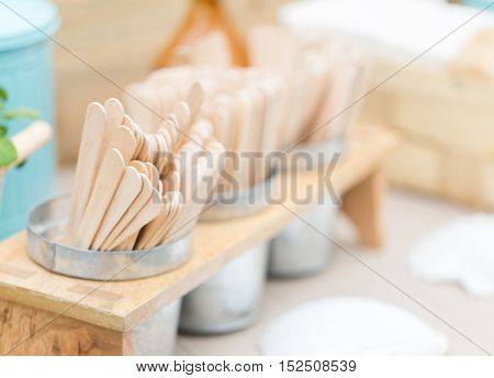 dishware and eating concept - close up of wooden ice cream sticks on restaurant table