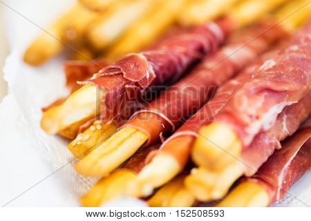food, catering, cooking and eating concept - close up of grissini bread sticks with prosciutto ham on serving tray