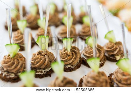 food, junk-food, catering and unhealthy eating concept - close up of canape with paste on serving tray