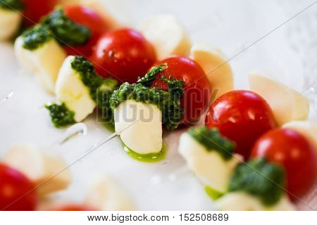 food, catering, cooking and eating concept - close up of mozzarella cheese and cherry tomato canape