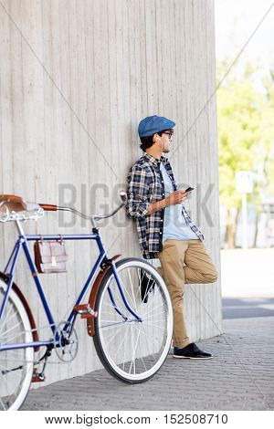 people, communication, technology and lifestyle - hipster man with smartphone, earphones and fixed gear bike listening to music on city street