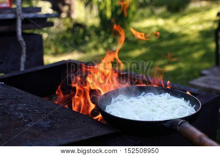 white cut onion fry on fire in oven outdoors in summer