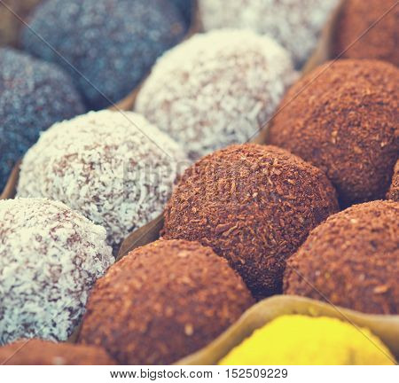 Colorful healthy homemade candies with nuts, dry fruits and spices, selective focus, toned