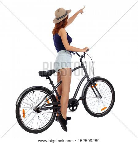 back view of pointing woman with a bicycle. cyclist sits on the bike. Rear view people collection.  backside view of person. Isolated over white background.
