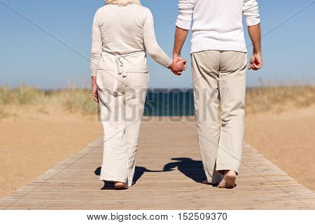 family, age, travel, tourism and people concept - close up of happy senior couple holding hands and walking on summer beach
