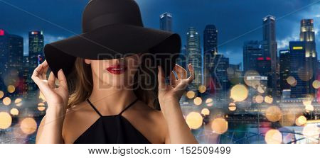 people, luxury and fashion concept - beautiful woman in black hat over nigh lights and singapore city skyscrapers background