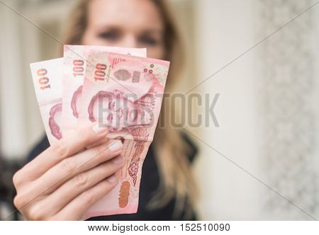 Closeup of woman's hand  holding cash withdrawn from ATM