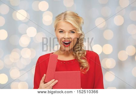 christmas, holidays, valentines day, birthday and people concept - happy excited woman in red dress with gift box over lights background