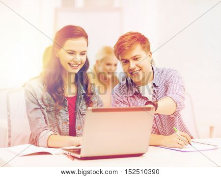 education, technology and internet concept - two smiling students with laptop and notebooks at school