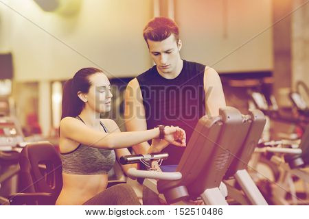 sport, fitness, lifestyle, technology and people concept - woman with trainer working out on exercise bike in gym