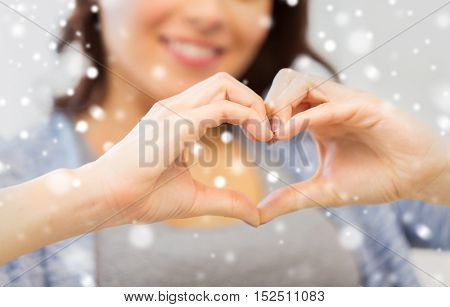 people, love, valentines day, christmas and  charity concept - close up of happy young woman showing heart with hands over snow