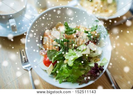 food, cooking and eating concept - close up of caesar salad on plate at restaurant or home