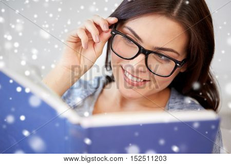 leisure, education, vision, winter and people concept - young woman in glasses reading book at home over snow