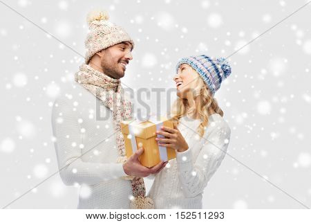winter, holidays, couple, christmas and people concept - smiling man and woman in hats and scarf with gift box