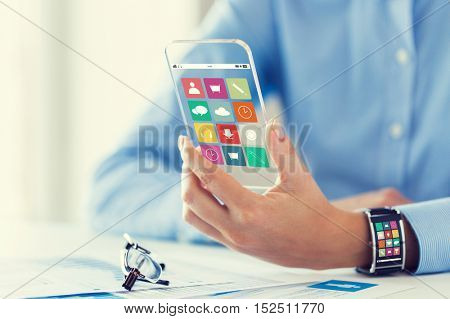 business, technology and people concept - close up of woman hand with application icons on transparent smartphone and smart watch screen