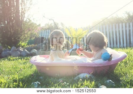 two small children bathe in a bathroom installed on the lawn in nature summer day