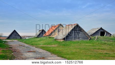 Typical rustic farm house in a village in Belarus. Wooden low sheds with pitched wooden and tiled roof.