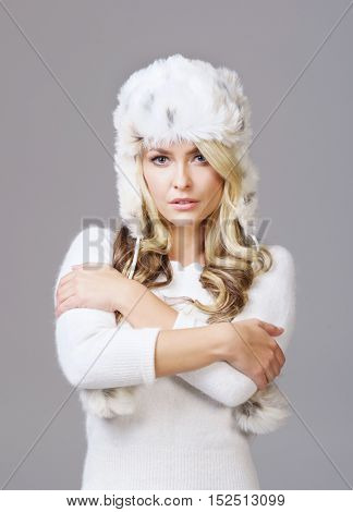 Portrait of young and beautiful woman in winter wear. Grey background. Christmas, xmas, x-mas concept.