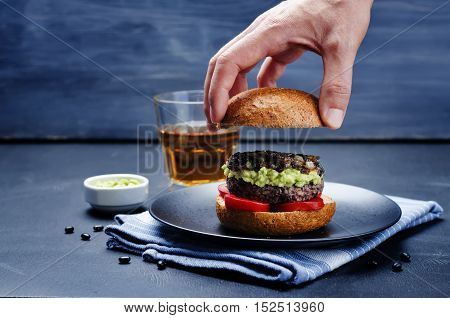 Men's hands holding the black bean burger with mashed avocado caramelized onions and tomatoes.