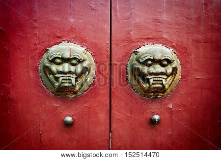 Traditional Chinese ancient architecture door red door and golden lion.