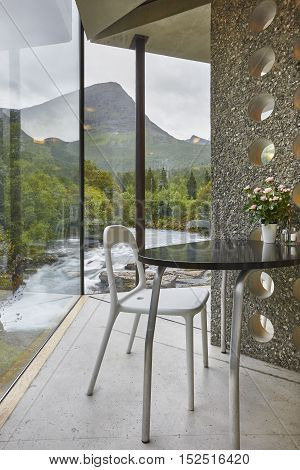 Norwegian landscape indoor viewpoint with table and chair. Norway. Vertical