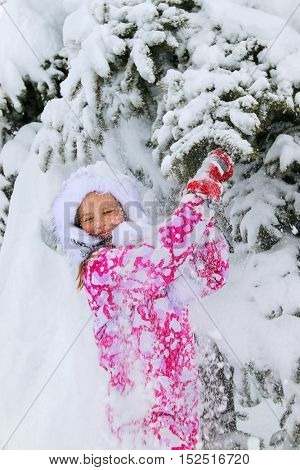 Little kid girl in winter clothes with falling snow near tree. snowy and cold winter has come.