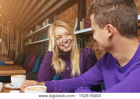 Loving young couple sitting in the cafeteria, talking and smiling. Drink hot coffee.