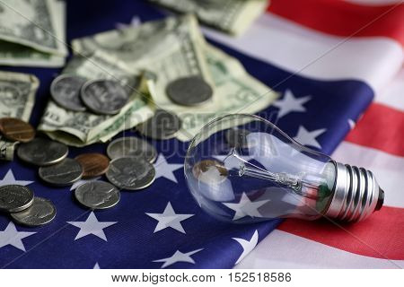 concept of excessive cost of electricity incandescent lamp and money on the table