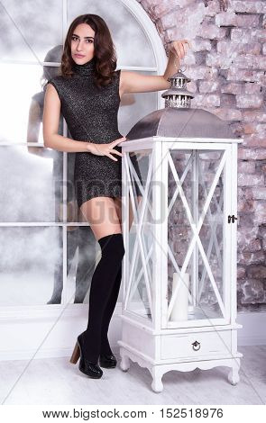 Lovely young woman posing with a vintage lamp. Christmas concept. Sexy girl in a short shiny dress and stockings.