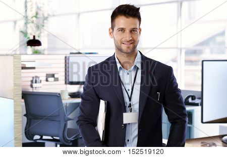 Portrait of handsome young confident businessman smiling happy to camera.