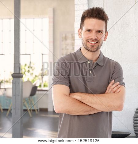 Happy casual man standing arms crossed at home, looking at camera.