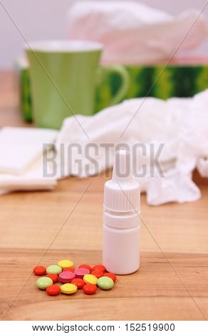 Pills and nose drops for colds used handkerchiefs and hot tea in background treatment of colds flu and runny