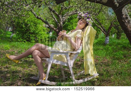 Pretty pregnant woman in a yellow dress and a wreath of flowers in spring blossoming apple orchard