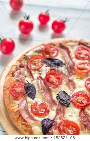 Pizza with cheese and prosciutto on the wooden board