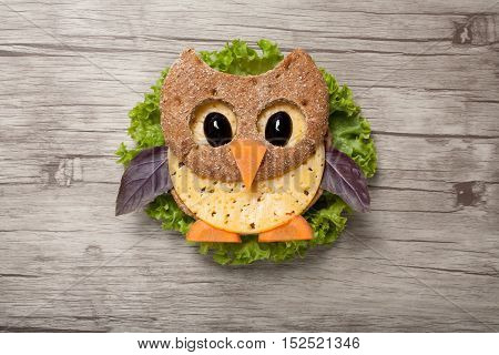 Owl made of bread and cheese on wooden background