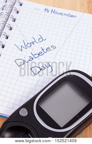 Glucometer And World Diabetes Day Written In Notebook