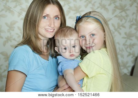 Happy three embracing family members posing for indoor portrait