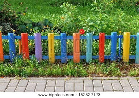 Small colorful wooden fence enclosing a bed of green plants.