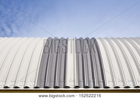Modern construction. Metal ribbed arch-span roof covering. Looking up front view.