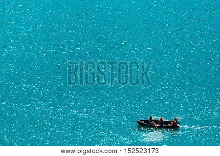 Unrecognizable people rowing in boat on lake vast water surface as copy space