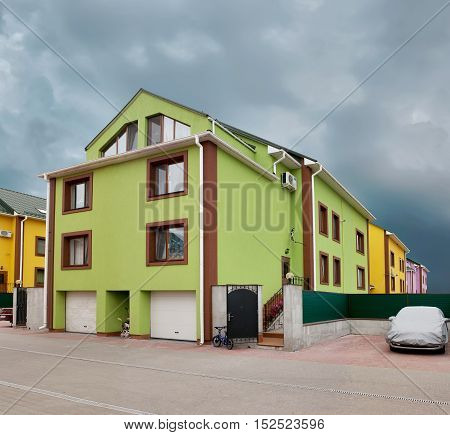 A three-storey residential building with light green walls against the gray sky