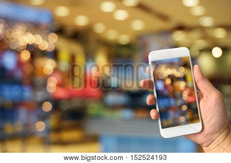 hand holding smart phone taking picture of blurred bokeh lights background in mall