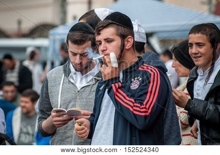 Uman Ukraine - 2 October 2016: Two young orthodox Jewish Hasidim during the New Year celebration in the streets of Uman. One smokes another reading religious literature.